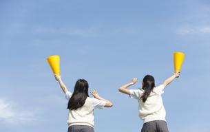 メガホンを持って応援する女子校生2人の後姿の写真素材 [FYI02813340]