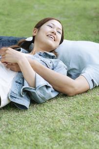 芝生で寝転ぶカップルの写真素材 [FYI02813355]