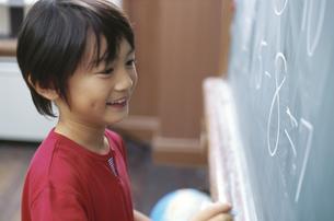 黒板に数字を書く男の子の写真素材 [FYI02813368]