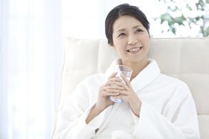 水を飲むバスローブの女性の写真素材 [FYI02813374]