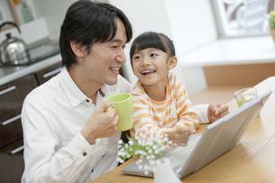 ノートパソコンを見て話す親子の写真素材 [FYI02813395]