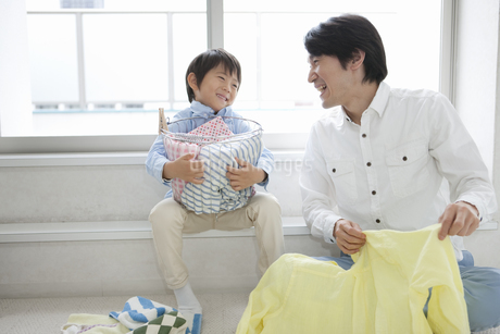洗濯物を畳む父親と息子の写真素材 [FYI02813396]