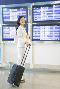 スーツケースを引いて歩くビジネスウーマンの写真素材 [FYI02813401]