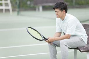 テニスコートで休憩する男性の写真素材 [FYI02813409]