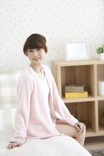 ベッドに座る笑顔の女性の写真素材 [FYI02813522]