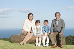 丸太に座っている祖父母と孫の写真素材 [FYI02813574]