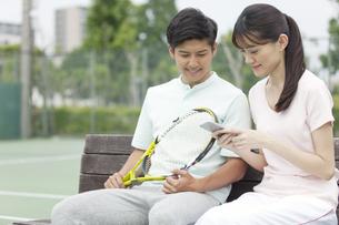 テニスコートで休憩するカップルの写真素材 [FYI02813575]