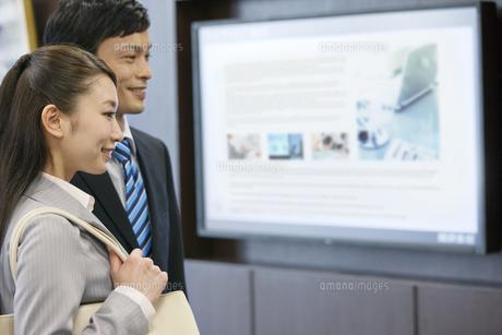 画面の前に立つビジネスマンとビジネスウーマンの写真素材 [FYI02813645]
