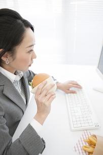 ハンバーガーを食べるビジネスウーマンの写真素材 [FYI02813672]