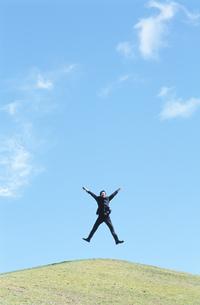 丘の上でジャンプするビジネスマンの写真素材 [FYI02813727]