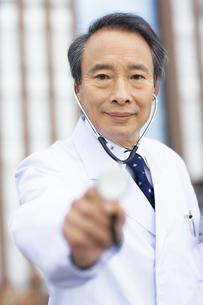聴診器を差し出す男性医師の写真素材 [FYI02813731]