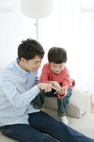 スマートフォンを持つ男の子と父親の写真素材 [FYI02813895]