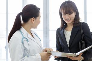 打ち合わせをする女医とビジネスウーマンの写真素材 [FYI02813909]