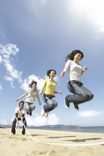 砂浜で大縄跳びをする若者達の写真素材 [FYI02813920]