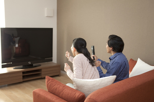 テレビ観戦をする中高年夫婦の写真素材 [FYI02813939]
