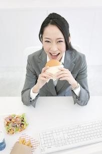 ハンバーガーを食べるビジネスウーマンの写真素材 [FYI02813971]