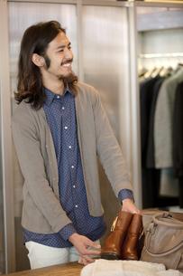 靴を持つ男性店員の写真素材 [FYI02813975]