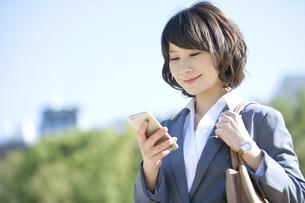 スマートフォンを操作するビジネスウーマンの写真素材 [FYI02813976]