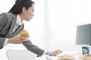 ハンバーガーを食べるビジネスウーマンの写真素材 [FYI02814270]