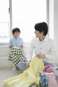 洗濯物を畳む親子の写真素材 [FYI02814349]