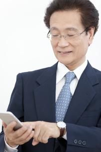 スマートフォンを操作するビジネスマンの写真素材 [FYI02814377]