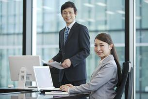 パソコンを操作するビジネスウーマンとビジネスマンの写真素材 [FYI02814404]