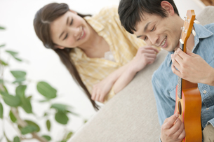 ウクレレを弾く男性と笑顔の女性の写真素材 [FYI02814420]