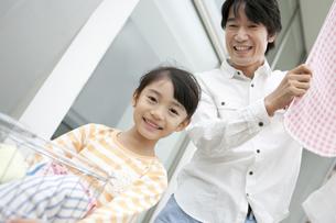 洗濯物を干す親子の写真素材 [FYI02814498]