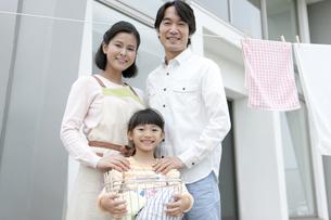 洗濯物を干す家族3人の写真素材 [FYI02814567]