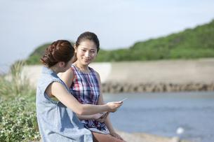 タブレットPCを見て会話する女性2人の写真素材 [FYI02814589]