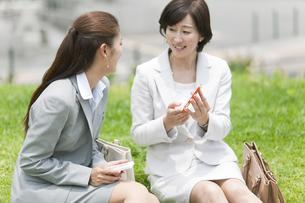 芝生に座って話すビジネスウーマン2人の写真素材 [FYI02814593]