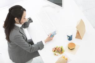昼食とスマートフォンを持つビジネスウーマンの写真素材 [FYI02814649]