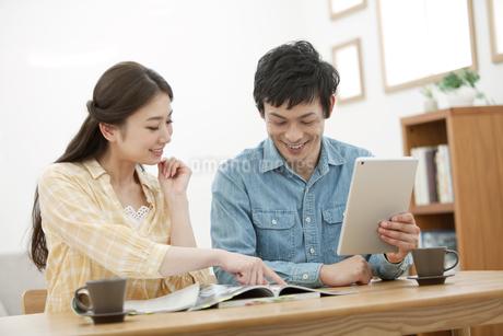 雑誌を見るカップルの写真素材 [FYI02814701]