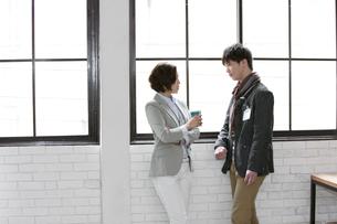 窓辺で話すビジネス男女の写真素材 [FYI02814748]