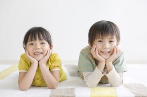 床に寝そべる男の子と女の子の写真素材 [FYI02814868]
