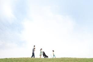 土手を歩く5人家族の写真素材 [FYI02814875]