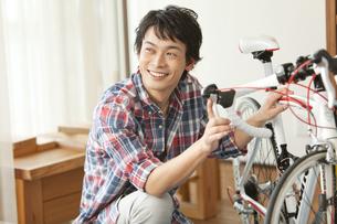 自転車の手入れをする男性の写真素材 [FYI02814887]