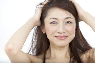 髪をかき上げる女性の写真素材 [FYI02814907]