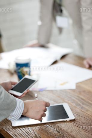 タブレットPCを操作するビジネス女性の手元の写真素材 [FYI02814909]