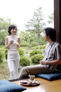 縁側に座る男性と佇む女性の写真素材 [FYI02814934]