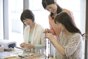 ハンドメイドアクセサリーを作る中高年女性3人の写真素材 [FYI02814970]