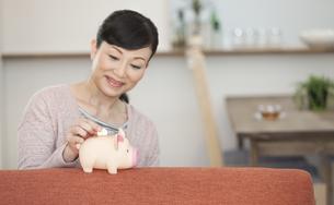 貯金箱にお金を入れる中高年女性の写真素材 [FYI02815022]