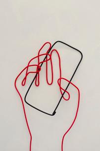 ワイヤーで作られたスマートフォンを持つ手のイラスト素材 [FYI02815047]