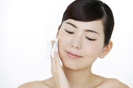 頬にコットンをあてる女性の写真素材 [FYI02815065]