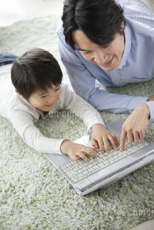 寝転んでノートパソコンを操作する親子の写真素材 [FYI02815148]