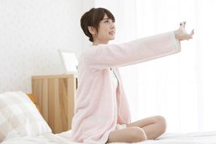 ベッドで伸びをする女性の写真素材 [FYI02815156]