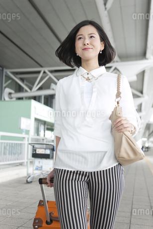 スーツケースを引いて歩く女性の写真素材 [FYI02815206]