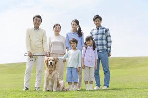犬と笑顔の3世代家族の写真素材 [FYI02815242]