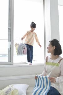 洗濯かごを運ぶ女の子と母親の写真素材 [FYI02815254]