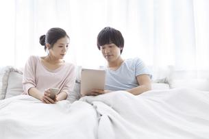 ベッドでくつろぐカップルの写真素材 [FYI02815406]